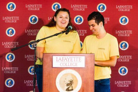 Students speak at a podium.