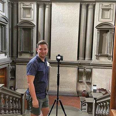 Eric Hupe stands at top of stairs in vestibule outside reading room of Michelangelo library