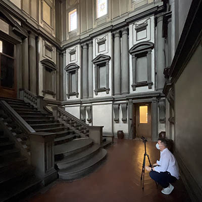 Eric Hupe crouches behind tripod at base of enormous staircase in vestibule designed by Michelangelo