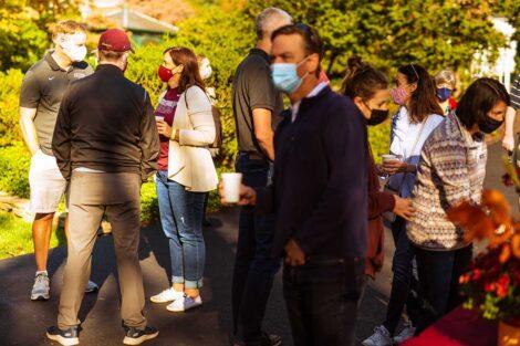parents in masks mingle outside