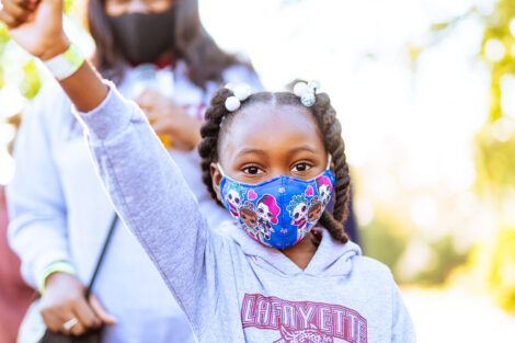 young Lafayette sibling in Lafayette sweatshirt and mask raises arm in the air
