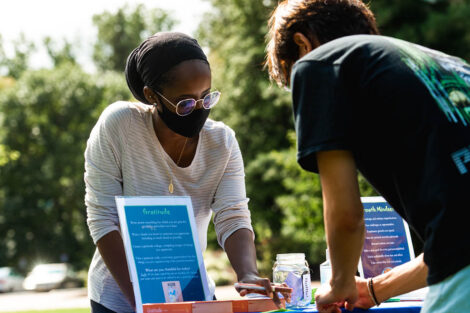 students gather at information table to learn about Thrive
