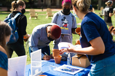 students gather at a table on the Quad to learn about Thrive