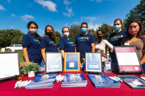 Counseling Center staff wears masks and stands at Thrive table at Quad event