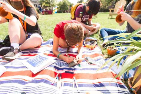 students in masks sit on blankets on the Quad and write messages