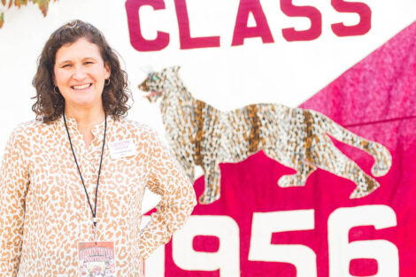 Nicole Hurd stands in front of a Class of 1956 flag.
