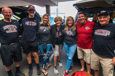 Families smile on Markle Parking Deck while tailgating.
