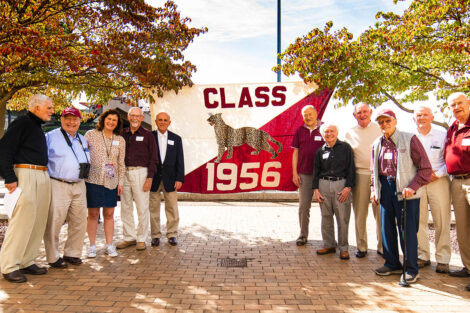 Members of the Class of 1956 stand in front of a flag.