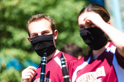 Two masked students hold clarinets