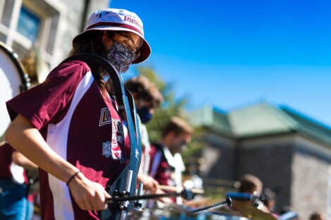 Masked student plays the drums in front of Hogg Hall.