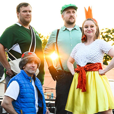Four cast members from Tall Green Plumber stand in costumes and stare off
