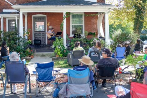 performer sings and plays guitar on a porch with audience in folding chairs
