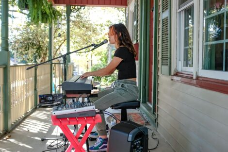 young person plays keyboard and sings on a porch