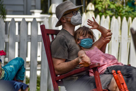 masked parent holds young masked child on rocking chair