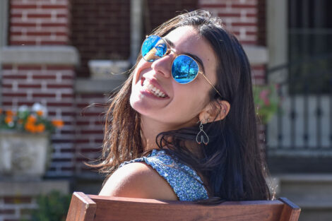 young person smiles wearing sunglases