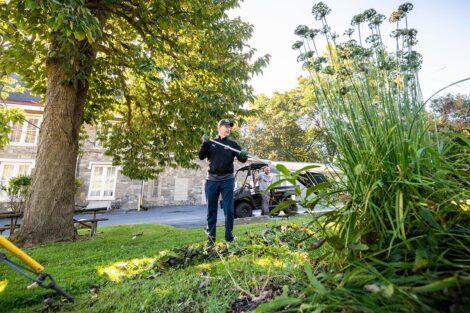 A staff volunteer tend to a garden.