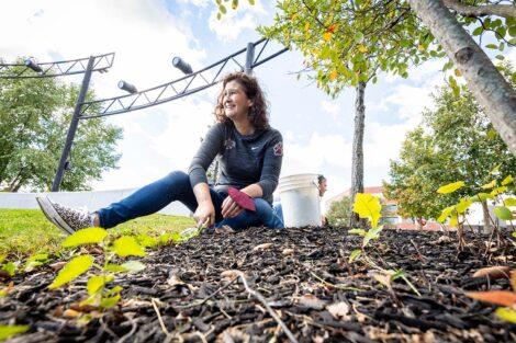 President Nicole Farmer Hurd sits in mulch of Riverside Park