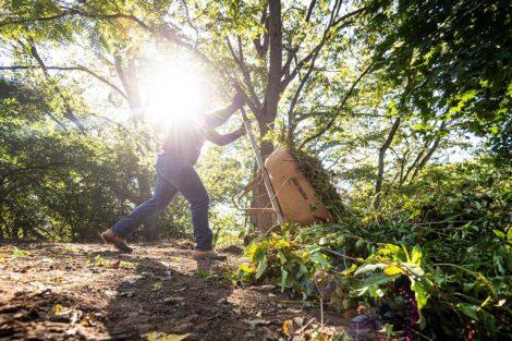 A staff volunteer dumps a wheelbarrow of dirt.
