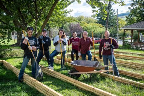 Staff volunteers smile while holding garden rakes and hoes..