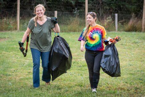 Two staff volunteers carry trash bags.