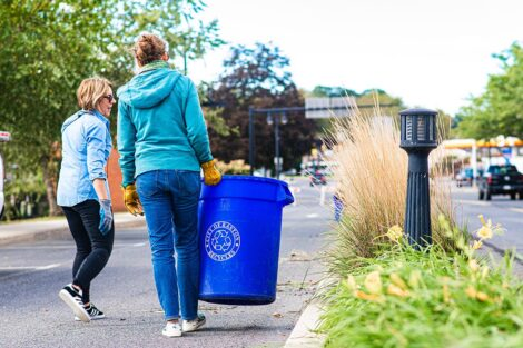 Staff volunteers carry a trash can.