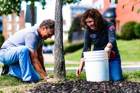 Bill Hurd and President Nicole Hurd pull weeds at Riverside Park.
