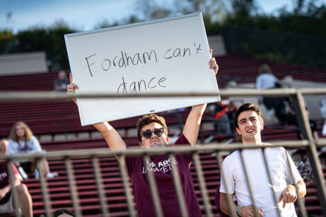 A student holds up a sign that says