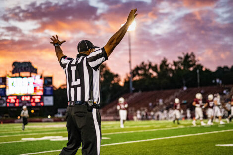A ref in front of a sunset on Fisher Field.