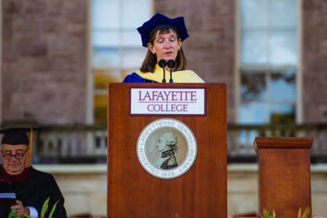 Alison Byerly wears academic regalia and speaks into microphone at podium