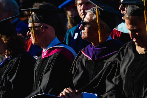 Alumni in academic regalia watch the ceremony