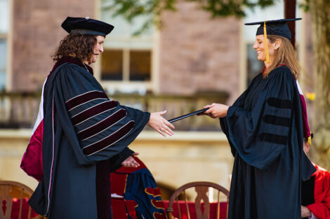 Linda Assante Carrasco '90, vice chair of the Board of Trustees, presented Nicole Farmer Hurd with with a copy of the charter and statutes of the College as a symbol of the presidential authority