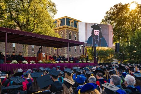 audience in academic regalia watches President Hurd deliver remarks on stage