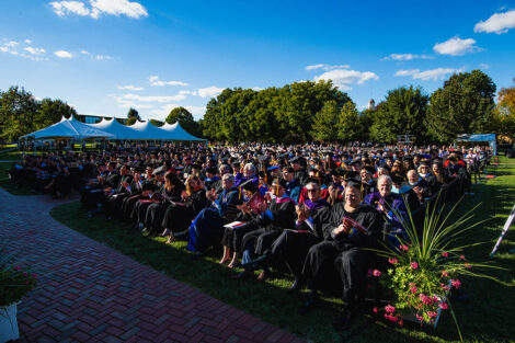 rows of people in academic regalia sit facing inauguration stage, blue sky, white tent in background