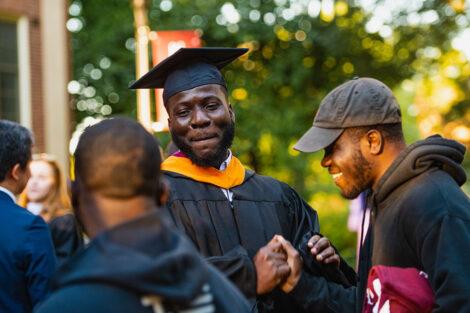 alumni smile after ceremony