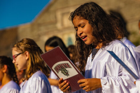 young children in white choir gowns sing
