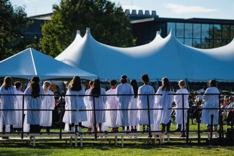 young children in white choir gowns sing with white tents behind them