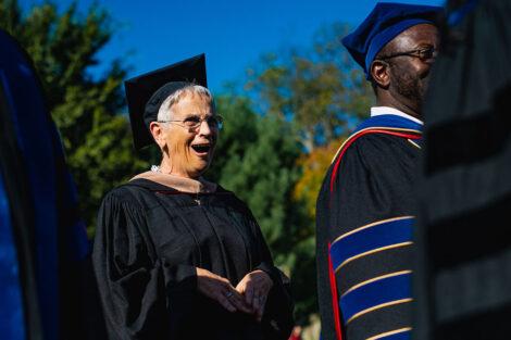 Prof. Rosie Bukas in academic regalia smiles.