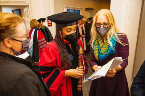 People in academic regalia look over a piece of paper.
