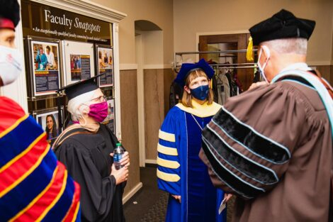 former President Alison Byerly chats with other members of the ceremony inside Markle Hall wearing academic regalia