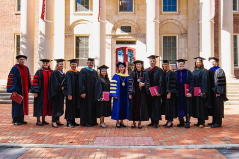 members of the platform party wear academic regalia standing in front of Markle Hall