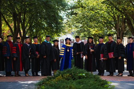 members of the platform party wear academic regalia and stand together