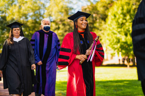A person in academic regalia smiles.