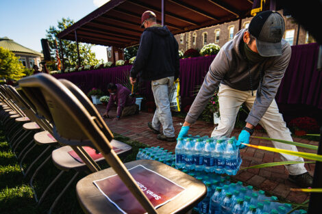 Staff members move cases of water.