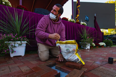 A Lafayette staff member fixes the brick path near the Inauguration stage.