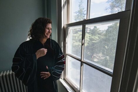 President Hurd has gown on and looks out window where sun is shining in and smiles