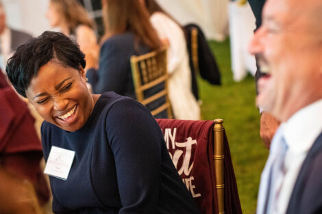 alums laugh while seated at a table
