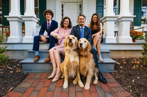 Hurd family with two golden retrievers on the steps in front of the president's residence