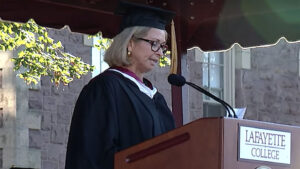 Tracy Hagert Sutka speaks into a microphone at a podium dressed in academic attire