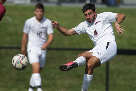 A soccer player kicks.