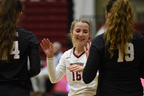 Volleyball player high fives others.